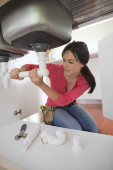 Woman working on pipes under kitchen sin...